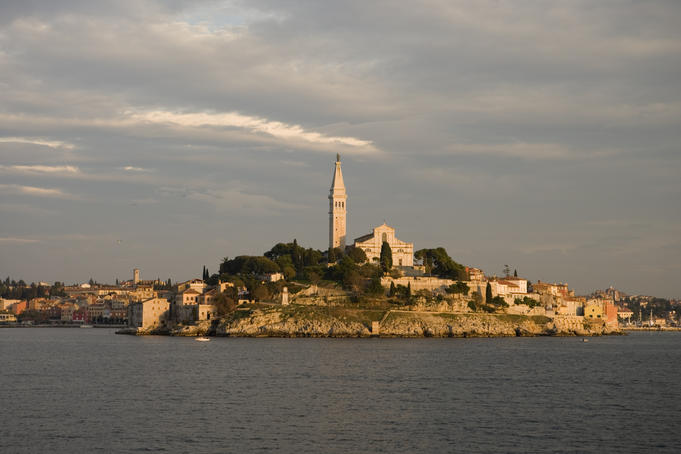 Rovinj town with Cathedral of St Euphemia on hilltop at sunset.
