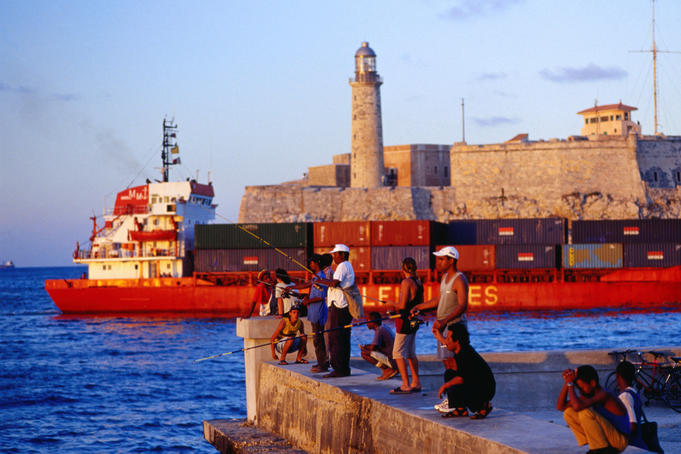 Fishing off the wharf in the Malecon across from the El Castillo del Morro, a cargo ship passing in between