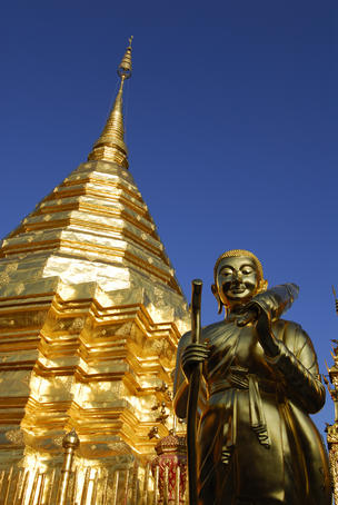 Statue and gilded stupa at Wat Phra That Doi Suthep temple.