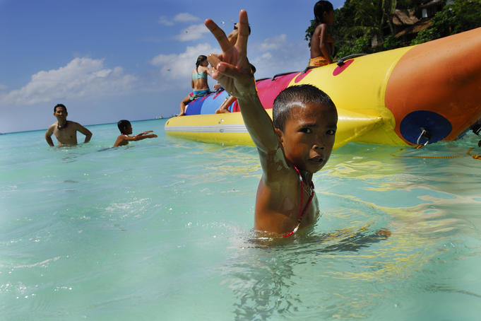 Boy giving the v sign while playing in Boracay's waters.