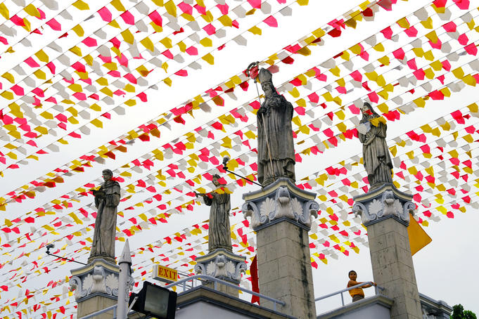 Statues at Basillica Minore del Santo Nino, with rows of flags overhead.
