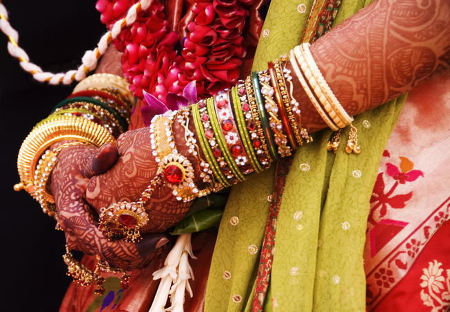 Bejewelled bride with henna hands at Mumbai wedding.