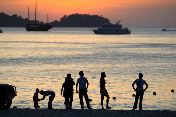 People on Patong Beach silhouetted at sunset.