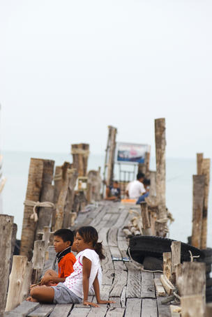 Children waiting for boats at pier.