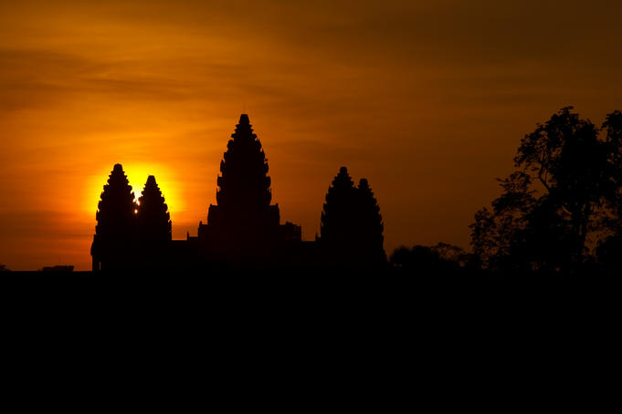 Sunrise silhouette of Angkor Wat through trees.