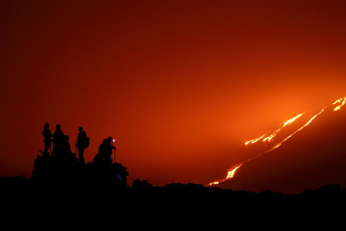 Climbers watching lava flowing down Pacaya Volcano.