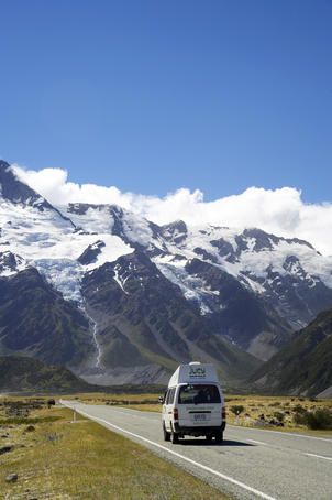 Campervan driving along road with Mt Sefton in background, Aoraki/Mt Cook National Park.