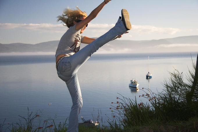 Girl high-kicking with sea in background.