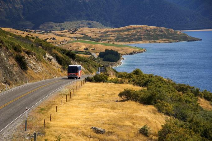 Tour bus climbing hill by Lake Wanaka.