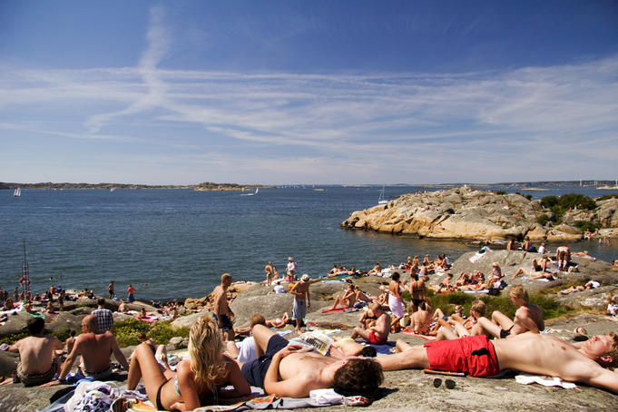 People sprawled on rocks by sea during summer.