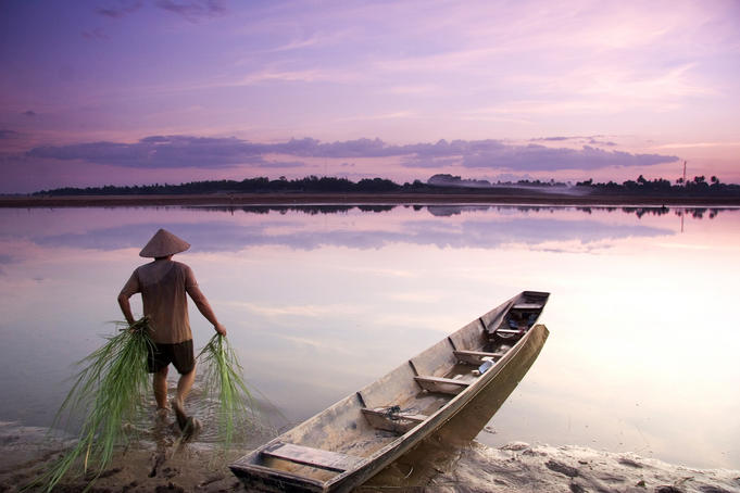 Lao man walking into calm river near canoe.