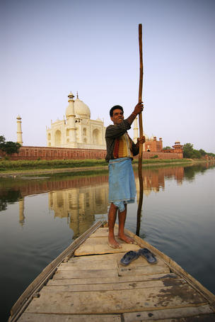 Boatman poling across Yamuna River beside Taj Mahal.