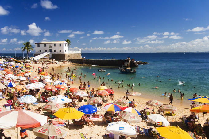 Beach umbrellas and bathers on the crowded beach of Porto da Barra, Salvador