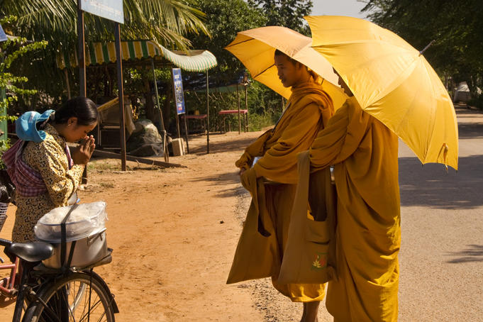 Woman receives blessing after offering alms to monks.