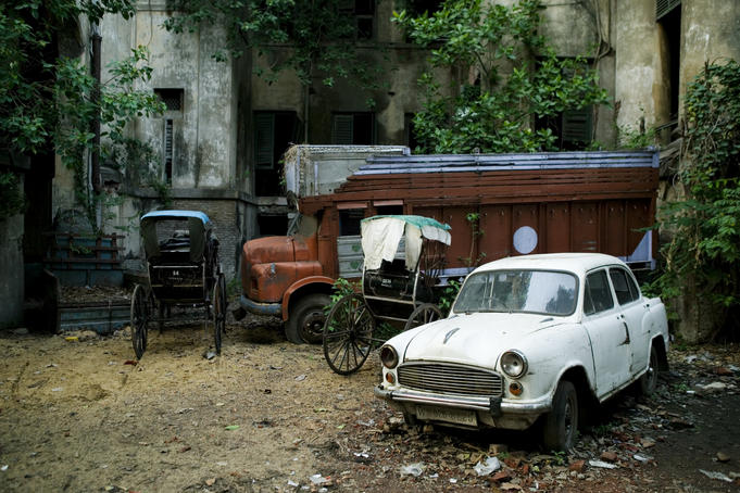 Rickshaws parked besides abandoned truck and car.