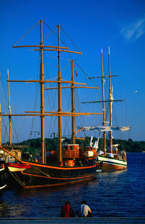 Old sailing ships on the harbour beneath a blue sky