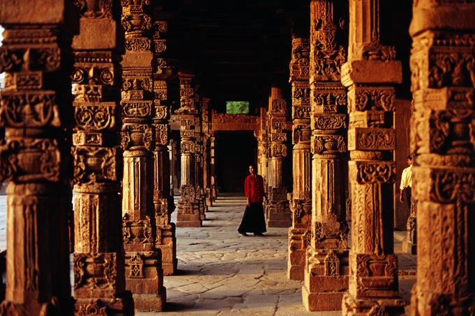 Young woman walking through sandstone pillars at Qutb Minar complex.