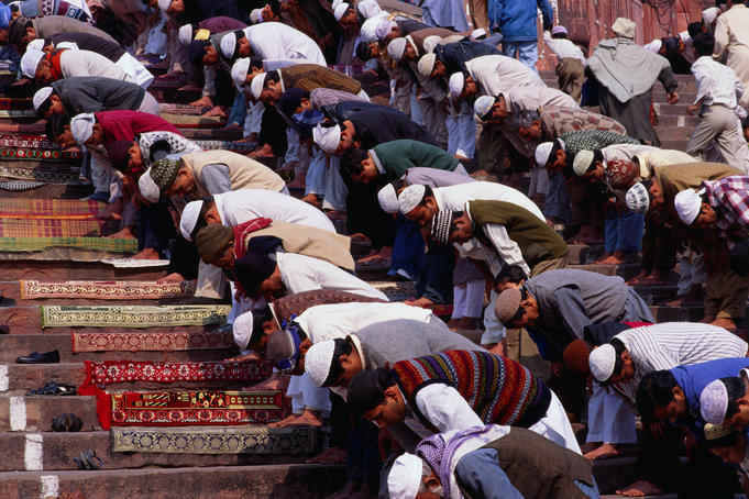 Men praying on steps of Jama Masjid during Friday midday prayers.