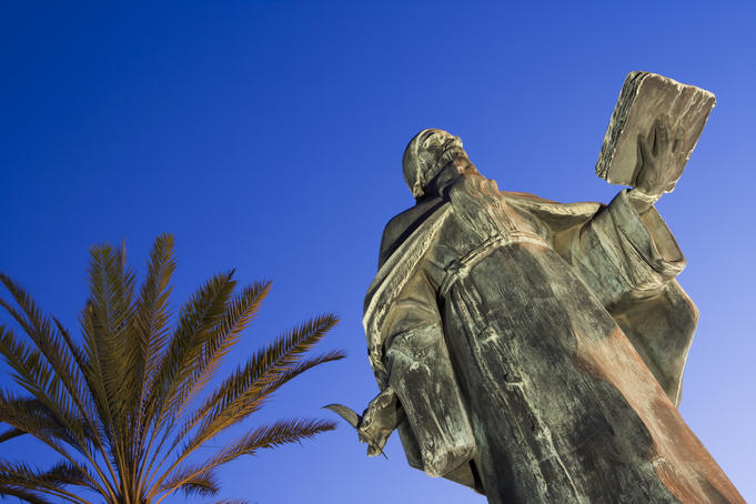 Statue of philosopher Ramon Llull in twilight.