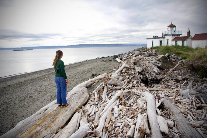 Woman standing on driftwood and looking towards Discovery Park Lighthouse.