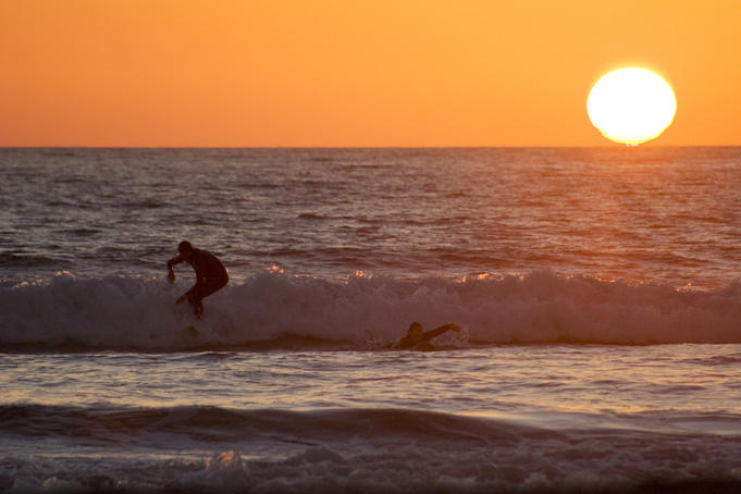 People surfing at late afternoon as the sun sets.