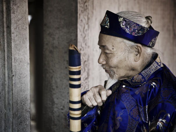 Old man in traditional costume at Temple of Literature.