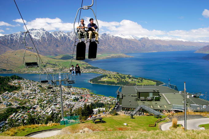 Luge riders taking lift up to top of hill, looking out over Queenstown and Lake Wakatipu.