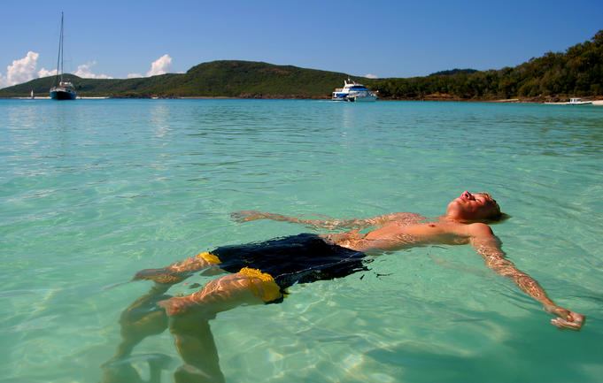 Man floating on his back in the Whitsunday's crystal clear waters.