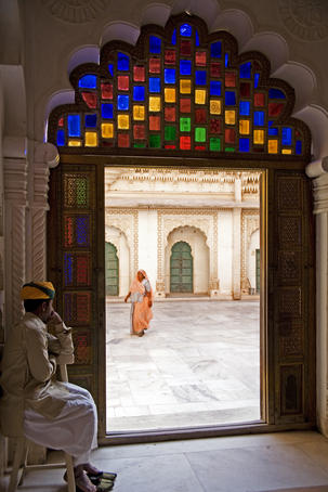 Palace guard and cleaner framed in doorway at Mehrangarh Fort.