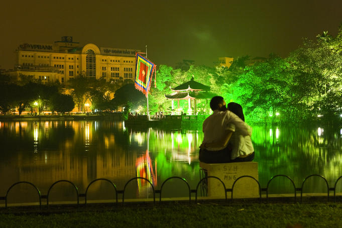 Couple hugging by Hoan Kiem Lake at night, Old Quarter.