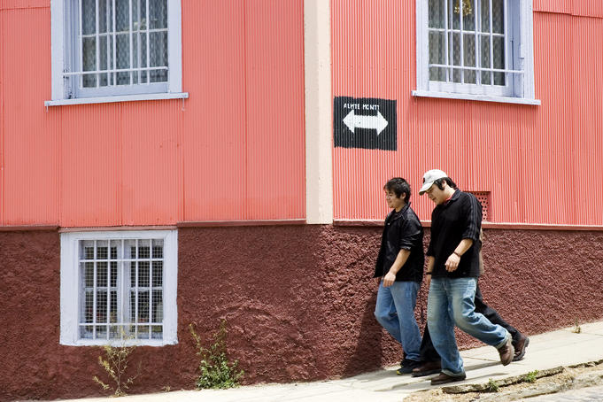 Group of young men walking past colourful building.