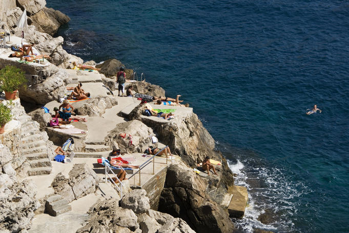 Swimmers and sunbathers enjoying the rocks outside the south wall.