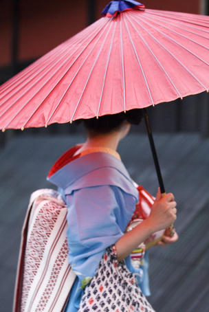 Geisha with umbrella in Gion district.