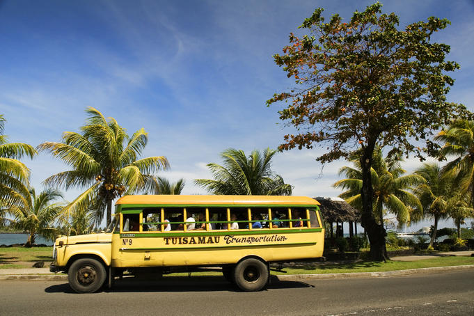 Bus with passengers driving along Beach Road, the main road of Apia.