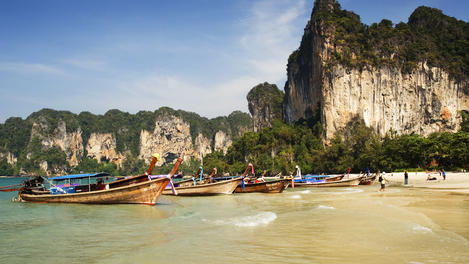 Limestone mountains and traditional longtail boats on beach.