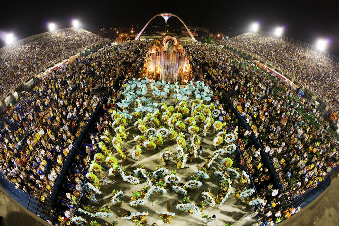 Samba schools parading towards the bird-shaped Sambodrome icon during Carnival.