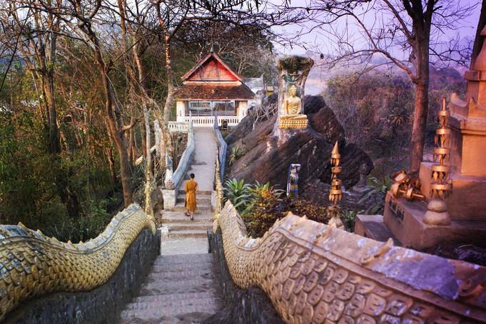Monk walking down staircase framed by serpent bodies at one of many temples on the slopes of Phu Si.
