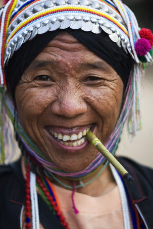 Portrait of woman from Akha tribe smoking a small cigar.