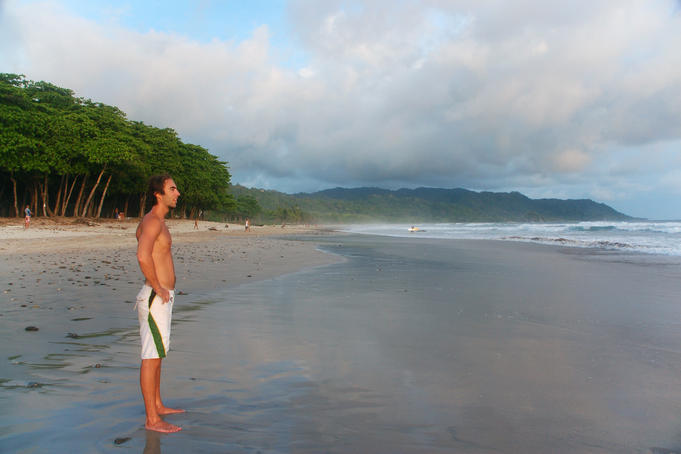 Man looking out to waves at misty tropical beach.