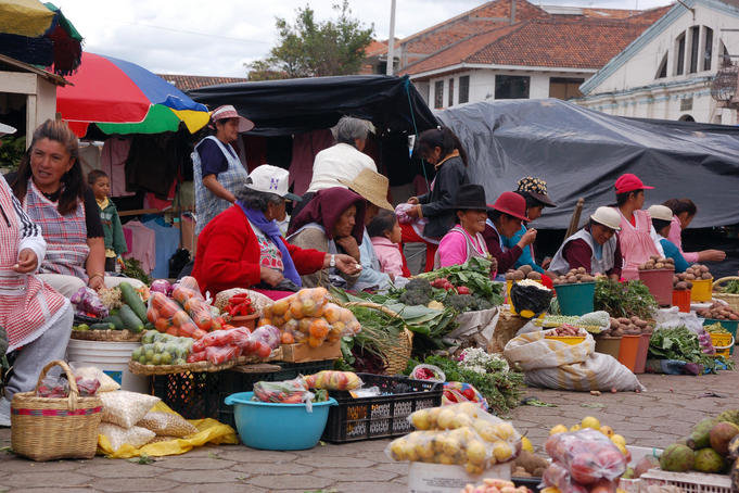 Vendors selling fruits and vegetables at outdoor market.