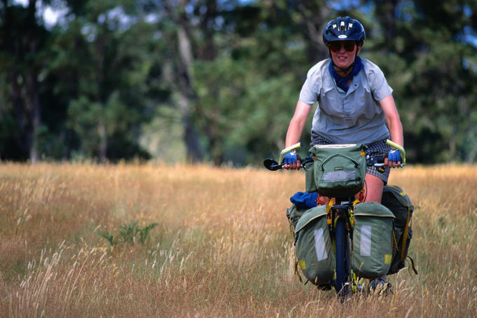 A touring cyclist in long grass on the Tasmanian Trail, an overland trail from Devonport to Hobart - near Quamby Brook, Tasmania