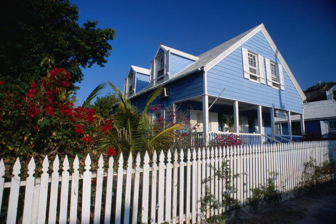 A pale blue wooden house with a white picket fence
