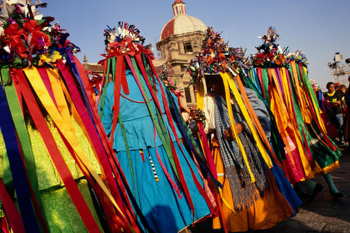 Native dancers from Tlaxcala, dressed in ribboned headwear, performing outside Basilica de Guadalupe.