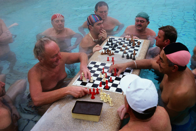 Men playing chess in the warm waters of the Szechenyi Baths.