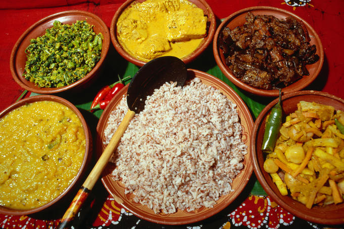 Clockwise from left; a typical dhal, green leafy vegetable, rice and curry meal of chicken, fried eggplant, pickled vegetables and red rice in the centre.
