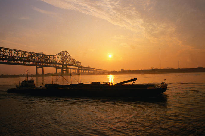 A barge on the Mississippi, silhouetted against the setting sun