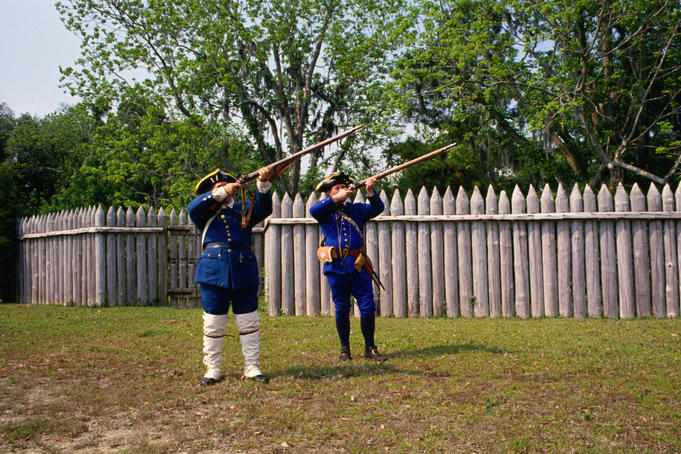 Two men dressed as Civil War soldiers, with rifles raised, taking part in an en-actment at Fort Maurepar