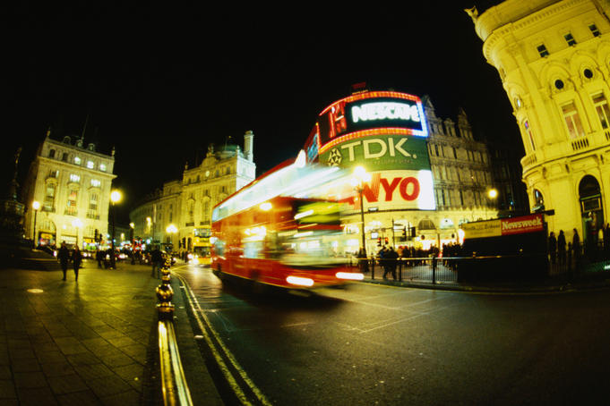 Double decker bus driving past illuminated neon signs of Picadilly Circus at night.