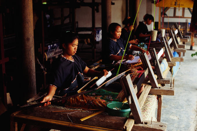 Women weaving on traditional looms in workshop producing traditional Ikat and Songket woven fabrics.