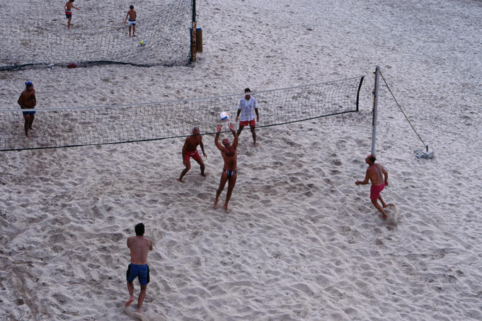 People playing beach volleyball on Prado Beach.